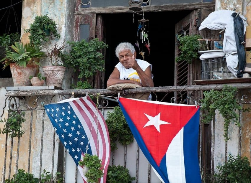 How to travel to Cuba - Cuban giving thumbs up from balcony (1)